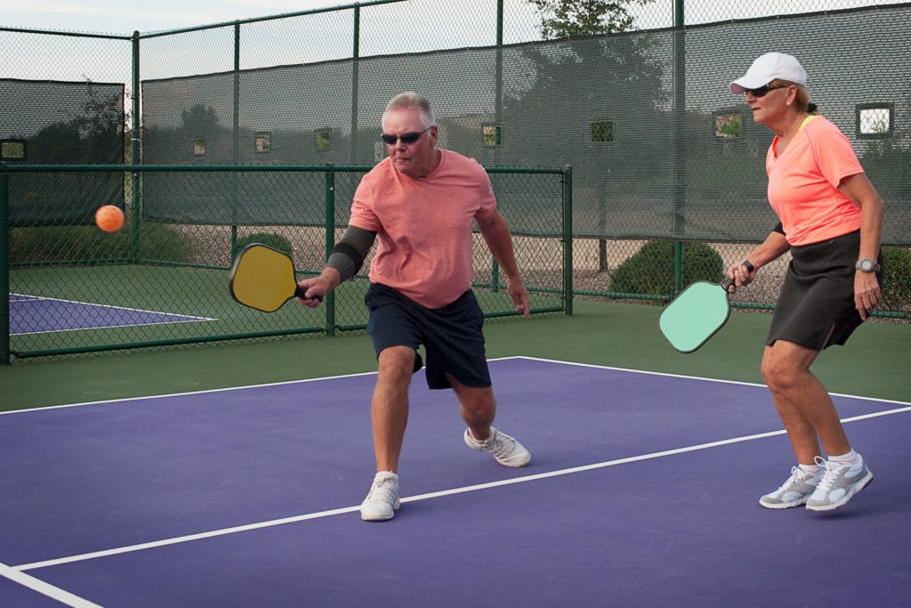 mixed doubles team playing in a pickleball match observing the double bounce rule