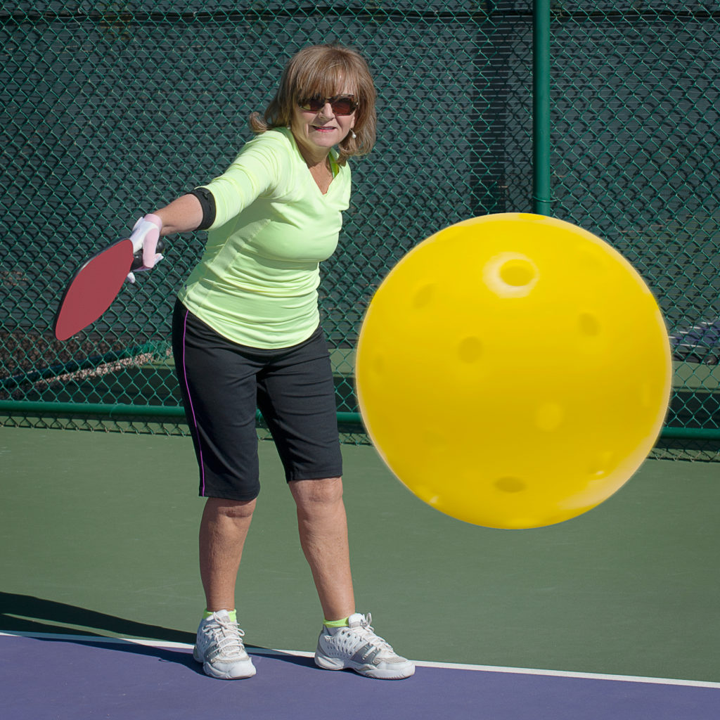 woman hitting pickleball - drilling using a pickleball machine