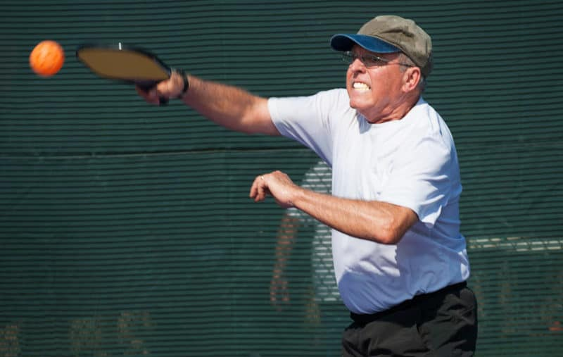 Senior pickleball player hit a overhead smash while gritting teeth.